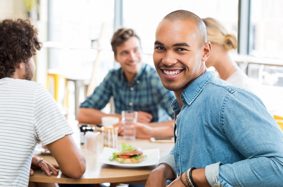 Portrait of happy african young man with his friends eating at c