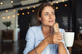 Thoughtful mature woman sitting in cafeteria holding coffee mug